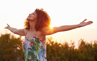 A young woman is lifting her arms up to the sky and enjoying life through spiritual development.