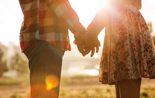 The sun is shining through a couple holding hands with love and confidence through couples coaching.